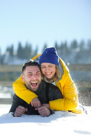 Young couple lies on snow. Sunny winter day. The guy and the girl joyfully laugh. Christmas holiday. Stock Photo
