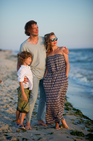 The young family admires a sunset on the sea coast. Light sea breeze. On faces pensive smiles. Stock Photo
