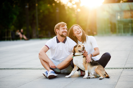Cute young couple sits on the earth closely having nestled to each other. Next to them good-natured beagle. Beautiful summer evening. Great mood. Stock Photo