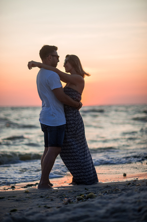 Couple of lovers stands having embraced on the seashore. Sunset, sea waves. Romantic appointment.