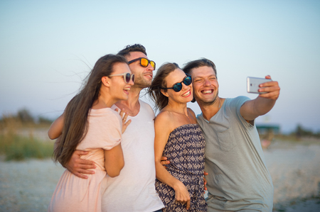 Group of cheerful young people photographed on the beach. Two guys and two girls posing on a background of sea waves. Friends in a good mood. All smiles. Foto de archivo