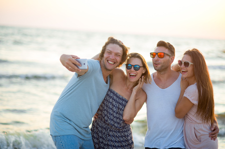 Group of cheerful young people photographed on the beach. Two guys and two girls posing on a background of sea waves. Friends in a good mood. All smiles. Stock fotó