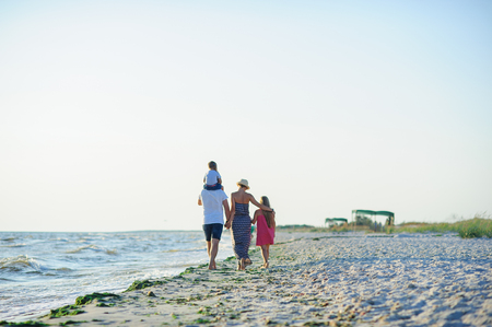 Family walks along the seaside. Desert beach, wet sand, sea waves. A unification with the nature.