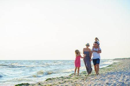 Happy family walks along the seaside holding hands. Dad, mom and two daughters. The younger girl sitting on the shoulders of his father. The blue sky, the sun, fresh sea wind. Pleasure from nature and communication. Stock Photo