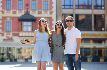 Three young people stand on the square of the ancient city. They are looking at beautiful buildings with pleasure. Friends are hugging each other. Everyone is in a good mood.