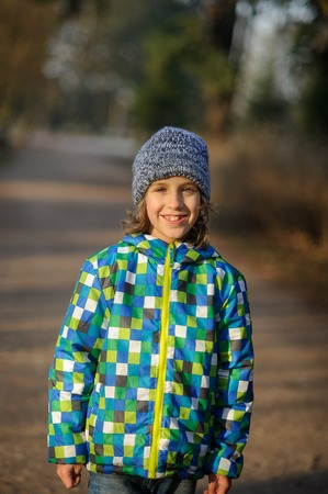 Portrait of a smiling boy of 9-10 years. The boy is dressed in a colorful jacket and a knitted cap.
