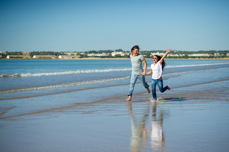 Happy couple running barefoot in the water. Summer, seaside, sun, blue sky. Young people holding hands. On their faces joyful smiles.