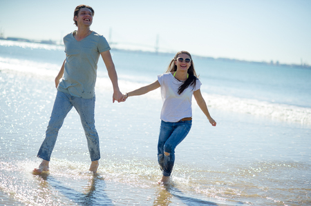 The guy and the girl running along barefoot by the water. Summer, seaside, sun, blue sky. Young people holding hands. On their face a happy smile.