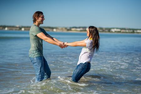 Glückliches junges Paar tanzt im Meer. Nasse Kleidung und Haare. Meer, Himmel, Liebe. Freude am Miteinander und an der Natur.
