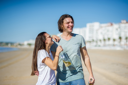 Cheerful young couple drinks wine on the beach. In hands at young people glass bottles with drink. They have an excellent mood. Stock Photo
