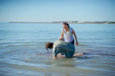 Jong koppel baden in de zee. Jongen en meisje spartelen vrolijk in het water. Stockfoto