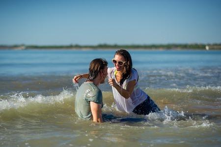 Junges Paar badet im Meer . Guy und Mädchen sind fröhlich im Wasser