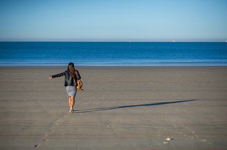 A woman admires the sea. She walks along the wet sand and looks into the distance. Blue sea, blue sky. Foto de archivo