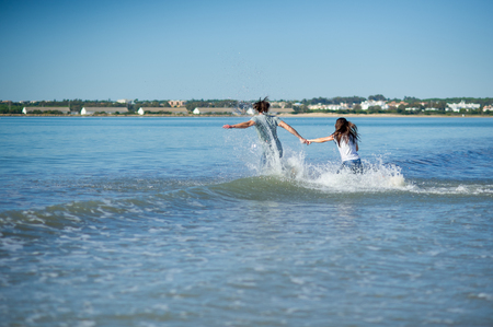 The young couple runs in the sea, raising splashes. The man and the woman hold hands. Picturesque landscape of the sea resort.