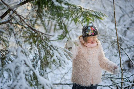 The girl of 8-9 years to shake on herself snow from a fir-tree. Walk in the winter wood. Pleasure for the child. Stock Photo