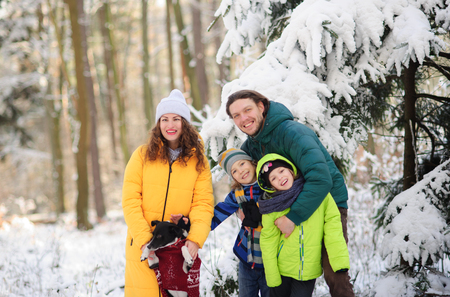 Family portrait in the winter forest. Happy family together with a pet against the background of snow-covered trees.