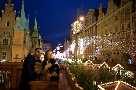 Christmas. Young couple from a balcony admires the festive city. Man and woman hold the pets in hands.