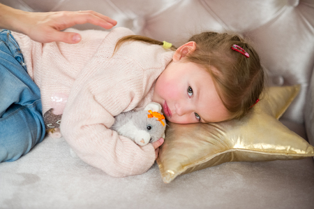Cute little girl falls asleep on a pink sofa. Child embraces a favourite soft toy.The mothers hand caresses the baby. Stock Photo