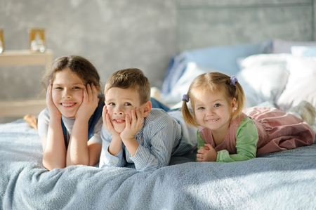 Two sisters and a brother. Three children from the same family are lying on the bed.