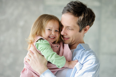 Father with the little daughter. The young man holds the little fair-haired girl on hands. He looks at the child with love and tenderness.