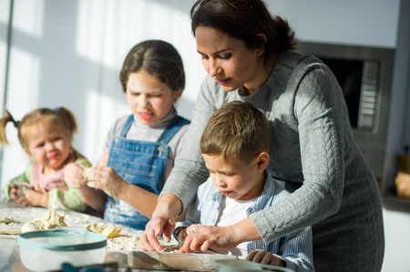 Mother teaches her children how to cook. Two girls and the boy very much try. Their faces in flour, dough has stuck to hands. Stockfoto