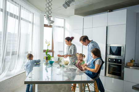 A family of five in the kitchen. Parents and children are cooking something. Useful and fun pastime. Imagens