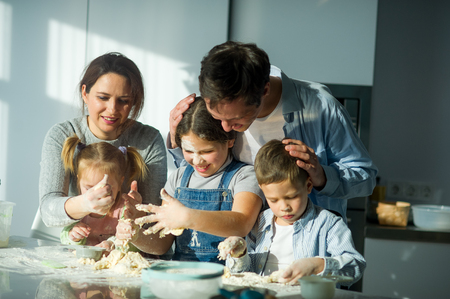 Large family prepares something of dough. Parents and three children at the kitchen table. Merry and useful pastime. Imagens