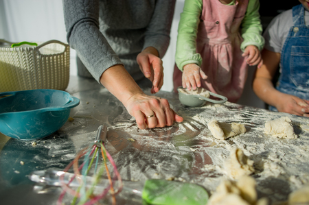 Mom teaches two little daughters to cook from dough. Children with pleasure are engaged in kitchen work. Фото со стока