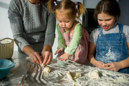 Mom teaches two little daughters to cook from dough. Children with pleasure are engaged in kitchen work. Imagens