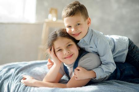 Twee kinderen, de jongen en het meisje, liggen op een bed. De jongere broer omarmt oudere zus als schouders. Kinderen hebben een goed humeur. Stockfoto
