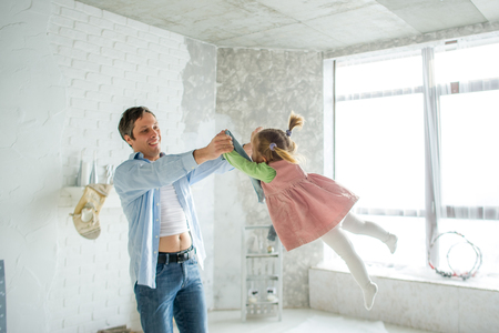 The father plays with the little daughter. The child laughs from pleasure. Imagens