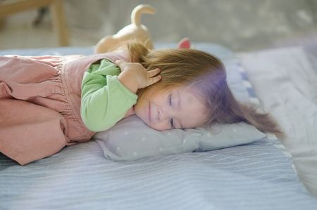 Little girl falls asleep on the bed. Next to the baby is a plush toy.