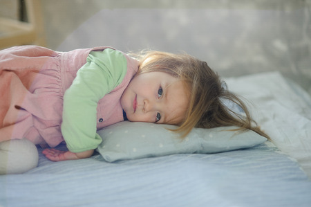 Little girl falls asleep on the bed. Baby is tired.
