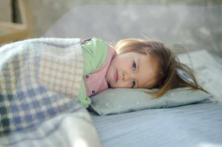 Little girl falls asleep on the bed. Baby is covered with a plaid.