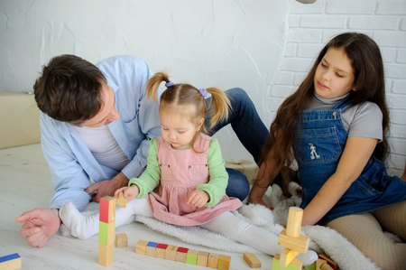 Father plays with two daughters. The man and the senior girl observe as the baby builds something of cubes. Imagens