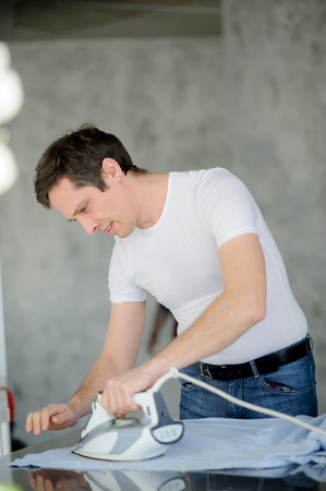 Young man irons a shirt. Dark-haired man in a white t-shirt and jeans skillfully irons a shirt on a table. Stock Photo