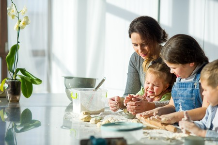 Mother teaches her three children to cook. Family is preparing something from the dough. There are necessary products on the kitchen table. Useful and fun pastime.