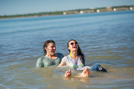 Young couple bathing in the sea. Guy and girl are merrily floundering in the water.