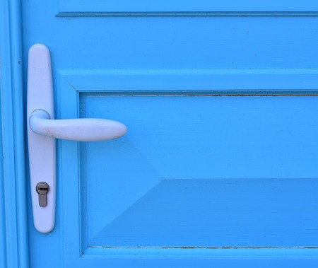 Detail of blue wooden door with handle and doorknob