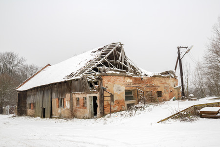 unsound: Ruined brickwooden house, destroyed roof, in winter snow