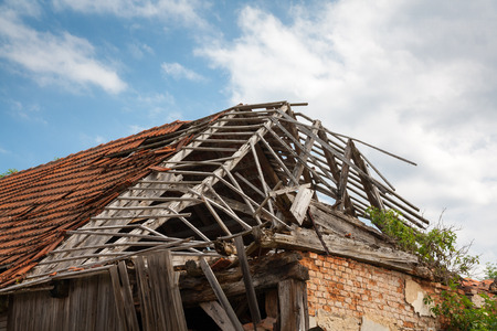 Ruined brickwooden house - destroyed roof, vegetation.