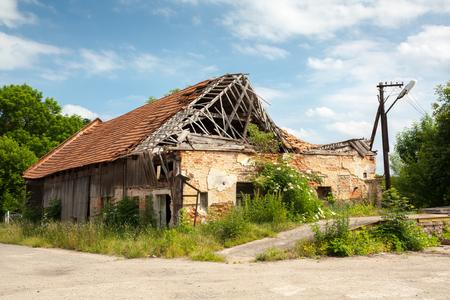 outbuilding: Ruined brickwooden house - destroyed roof, vegetation.