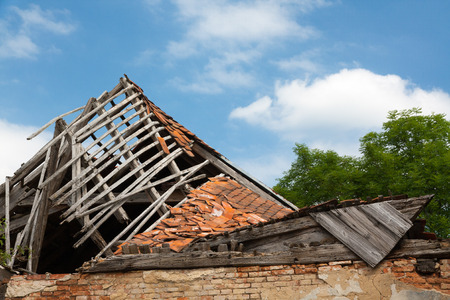 unsound: Ruined brickwooden house - destroyed roof. Stock Photo
