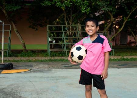 Little boy holds soccer ball.