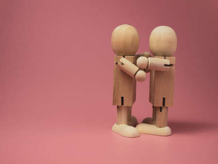 2 wooden dolls hugging each other on a pink background.Concept of social contact from wooden dolls.