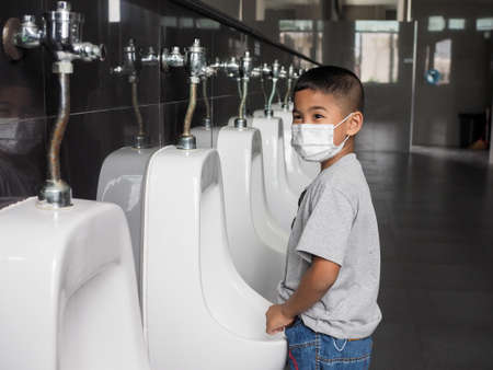 Boy wearing a protective face He is urinating in the public toilet.
