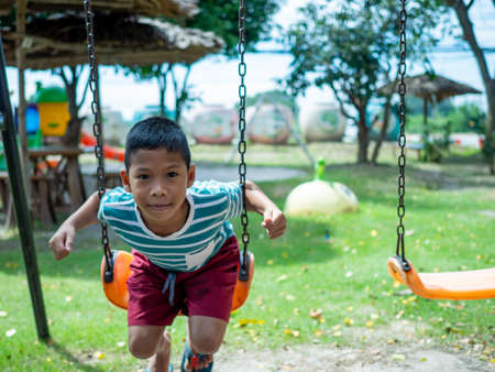 A boy sitting on a swing In the playground