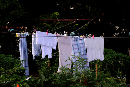 laundry line: The sun shining in the blue sky Colorful clothes hanging to dry on a laundry line