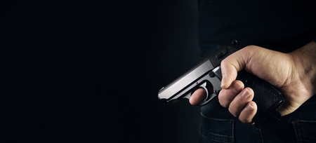 Hand shooting gun on black background killer concept. 스톡 콘텐츠