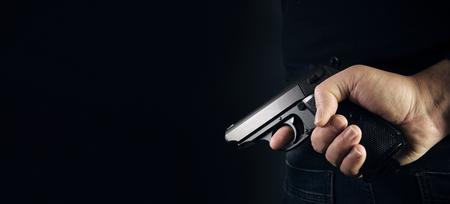 Hand shooting gun on black background killer concept. Stock Photo